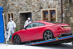 © Licensed to London News Pictures . 17/01/2016 . Rossendale , UK . A red Audi TT is towed from outside the house at the scene on Sunny Bank Road , Helmshore , where 60-year-old Sadie Hartley was discovered with multiple stab wounds at her home at 22:40 GMT on Friday (15th January 2016) . Photo credit : Joel Goodman/LNP