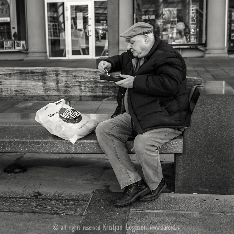 Man sitting on a granit bench on Torgalmenningen early spring in central Bergen eating his lunch he just bought in Leroy food shop