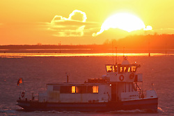 © Licensed to London News Pictures. 07/04/2016. Sunrise seen this morning over the Thames at Gravesend in Kent. Passenger ferry seen crossing from Tilbury, Essex, to Gravesend in Kent. Credit : Rob Powell/LNP