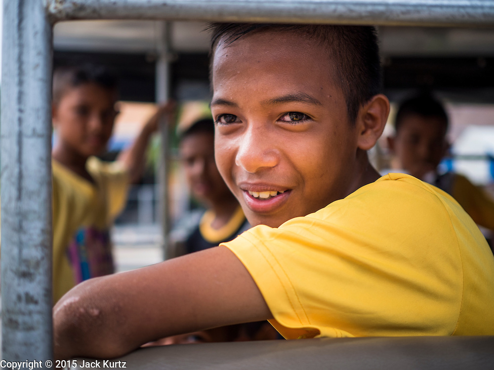 14 JUNE 2015 - NARATHIWAT, NARATHIWAT, THAILAND:  A Thai Muslim student in a pickup truck before leaving a food distribution in Narathiwat. The food distribution is done every year before  Ramadan, which starts June 18. The annual food distribution event is organized by the Southern Peace Media Club, a group of Thai journalists who work in the southern provinces of Pattani, Narathiwat and Yala. An insurgency pitting Muslim extremists against the Thai government has rocked Thailand's southern three provinces since 2001. More than 6,000 people have been killed in the sectarian violence.   PHOTO BY JACK KURTZ