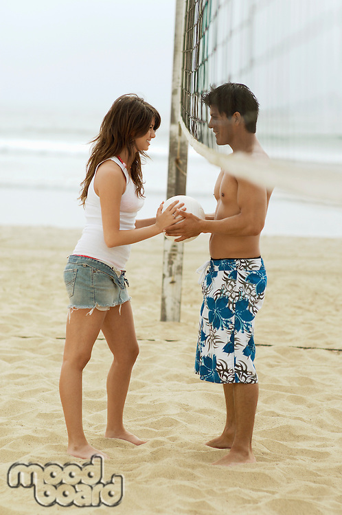 Couple Both Holding Volleyball under Net on Beach