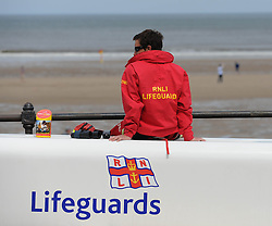 © Licensed to London News Pictures. 27/05/2013..Saltburn, England..RNLI Lifeguard Kris Fairest keeps a watchful eye on the beach during the warm bank holiday weather at Saltburn by the Sea in Cleveland....Photo credit : Ian Forsyth/LNP