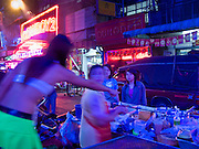 "29 FEBRUARY 2008 -- BANGKOK, THAILAND:  A push cart food vendor does business with workers on Soi ""Cowboy"" one of the adult entertainment districts in Bangkok, Thailand.   Photo by Jack Kurtz/ZUMA Press"