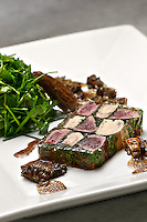 Venison and Foie gras Terrine, parsley salad the side, white plate on a gray marble table, MEDIUM SHOT