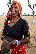 Choti Devi, aged 63, poses for a portrait in her field in Balaji ki Dhani, Bauli, Nagaur District, Rajasthan. Barefoot solar engineer Santosh Devi who graduated from a  solar course in the Barefoot College in Tilonia, Ajmer, Rajasthan, India, had provided Choti Devi with solar power and lanterns improving her life by allowing her to protect herself from poisonous monsoon insects and work late in the fields, cook in the night, and protect her cattle when they return from grazing after sunset. Photo by Suzanne Lee for Panos London
