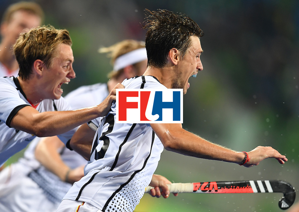 Germany's Florian Fuchs (R) celebrates his team's third goal during the men's quarterfinal field hockey Germany vs New Zealand match of the Rio 2016 Olympics Games at the Olympic Hockey Centre in Rio de Janeiro on August 14, 2016. / AFP / MANAN VATSYAYANA        (Photo credit should read MANAN VATSYAYANA/AFP/Getty Images)