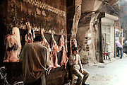 A butcher in Aleppo's souq waits for customers. The meat he sells is hanged on one of the gates of the souq