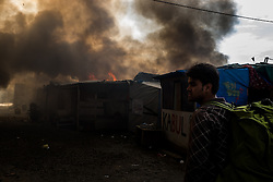 October 26, 2016 - Calais, France - A Migrant looks in the in the Calais Jungle at the burning huts, on October 26, 2016. Huge fires destroyed a mayor part of the refugee camp today. (Credit Image: © Markus Heine/NurPhoto via ZUMA Press)