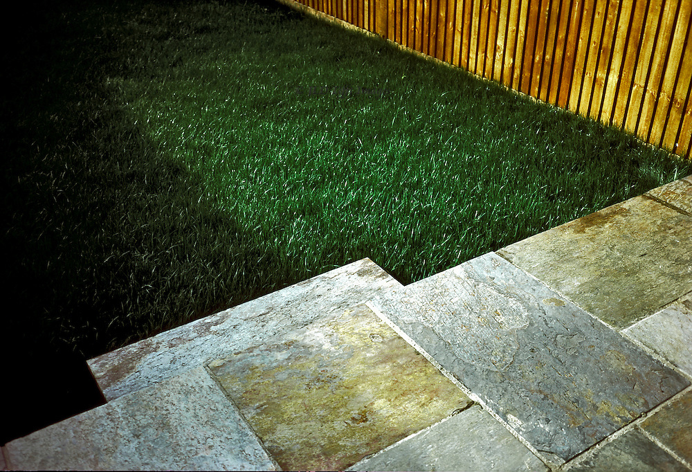 Design in sharp angles formed by wooden fence in vertical slats, green grass lawn, and patterned stone slabs of a terrace.  All seen in partial view.