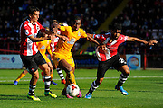 Uche Ikpeazu (26) of Cambridge United battles for possession in the 18 yard box with Craig Woodman (3) of Exeter City and Luke Croll (29) of Exeter City  during the EFL Sky Bet League 2 match between Exeter City and Cambridge United at St James' Park, Exeter, England on 22 October 2016. Photo by Graham Hunt.