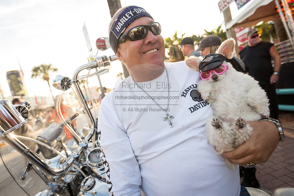 A biker sits with his poodle dressed in a Harley hat and glasses alongside Main Street during the 74th Annual Daytona Bike Week March 8, 2015 in Daytona Beach, Florida. More than 500,000 bikers and spectators gather for the week long event, the largest motorcycle rally in America.