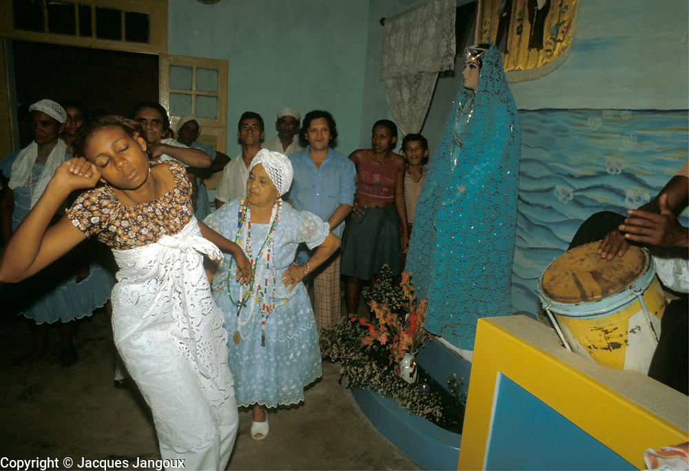 Mina (popularly batuque) Afro-Brazilian spirit possession cult, syncretic with the Catholic religion, in Belem, Para, Brazil. Girl spectator and believer is in trance, possessed by a spirit, to the sound of drums. The mae de santo or cult leader is watching, ready to attend the spirit. Image dressed in blue is of deity Yemanja.