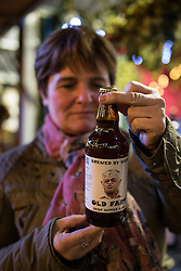 "© Licensed to London News Pictures . Manchester , UK . A woman looks at "" Old Fart "" novelty beer , sold by one of the stalls . FILE PHOTO DATED 20/11/2013 of Christmas Markets in Manchester as temperatures drop and 2014 seasonal markets start up across the country , selling mulled wine , german hot dogs , dutch pancakes , wooly hats and many other festive frivolities . Christmas markets provide an economic boost to many city centres and create a festive atmosphere on otherwise cold and dark nights . . Photo credit : Joel Goodman/LNP"