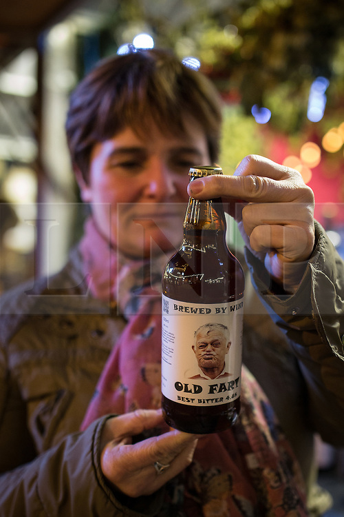 """© Licensed to London News Pictures . Manchester , UK . A woman looks at """" Old Fart """" novelty beer , sold by one of the stalls . FILE PHOTO DATED 20/11/2013 of Christmas Markets in Manchester as temperatures drop and 2014 seasonal markets start up across the country , selling mulled wine , german hot dogs , dutch pancakes , wooly hats and many other festive frivolities . Christmas markets provide an economic boost to many city centres and create a festive atmosphere on otherwise cold and dark nights . . Photo credit : Joel Goodman/LNP"""