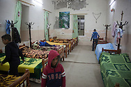 15/11/14. Alqosh, Iraq. Milad lays on his bed as Wassam (left) and some of the 8 orphans they share a room with tidy their dormitory.