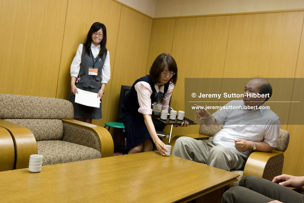 Office worker brings tea to a local council worker, Setana, Hokkaido, Japan.  July, 2008.