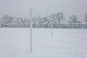 Cancelled football and empty landscape of snowbound goal posts in wintry public park in south London.