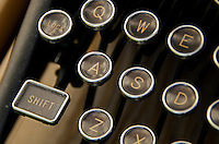 Closeup of antique typewriter keys, including the shift key.