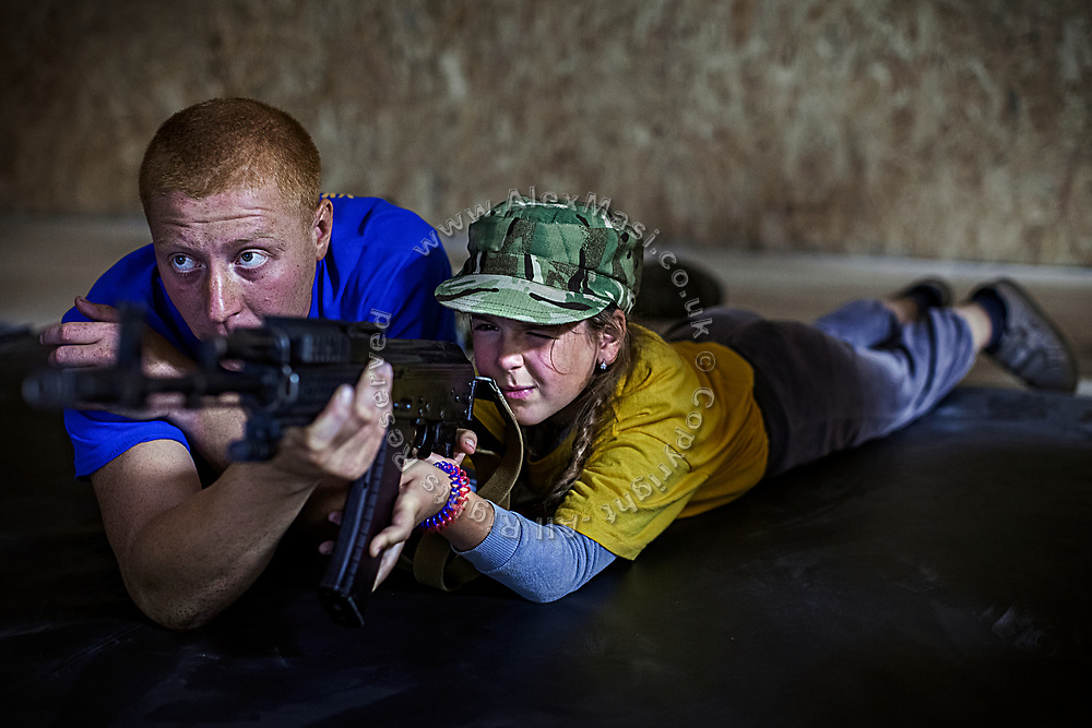 A young girl participating to the ultra-nationalistic Azovets children's camp is practicing shooting with a professional simulator, while assisted by Gold, 27, her instructor, on the floor of a former tank factory, now functioning as training base and repairs workshop near the village of Buzova, 30 km west of Kiev, the capital of Ukraine.