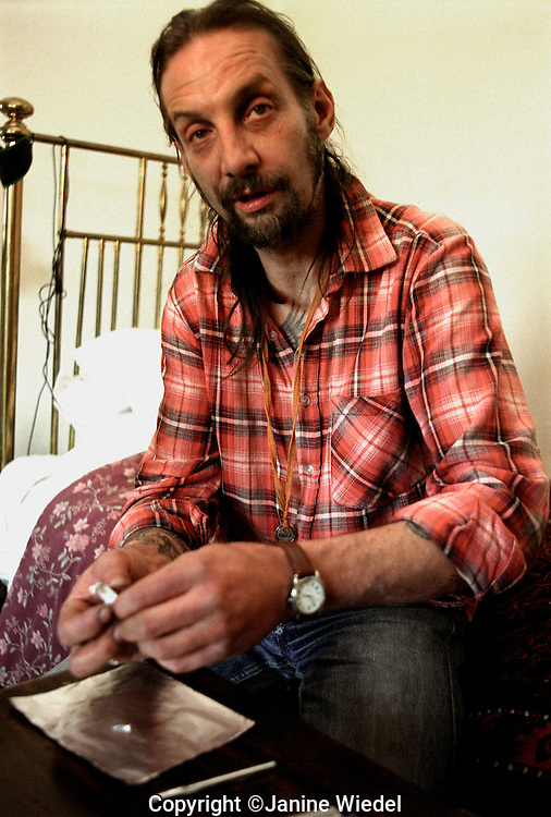 A drug addict preparing to smoke heroin.