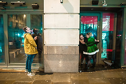 "© Licensed to London News Pictures . 22/12/2018 . Manchester , UK . A man and a woman urinate in adjacent doorways on Withy Grove . Revellers out in Manchester City Centre overnight during "" Mad Friday "" , named for historically being one of the busiest nights of the year for the emergency services in the UK . Photo credit : Joel Goodman/LNP"