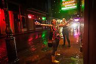New Orleans, Louisiana, August 28th, 2012, Women drinking hurricanes in the rain on Bourbon Street as Hurricane Isaac makes landfall as a category hurricane.