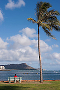 A man sits on a bench looking at Diamond Head from Ala Moana Beach Park.