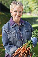 Senior woman holding freshly picked carrots outdoors, portrait
