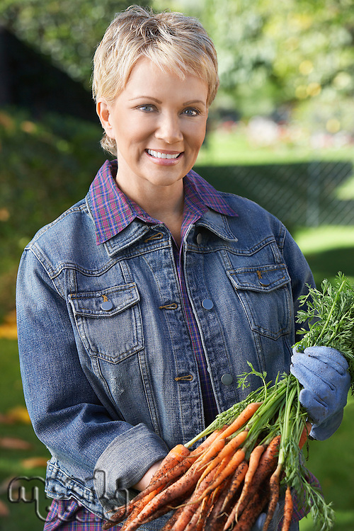 Senior woman holding freshly picked carrots outdoors, portrait