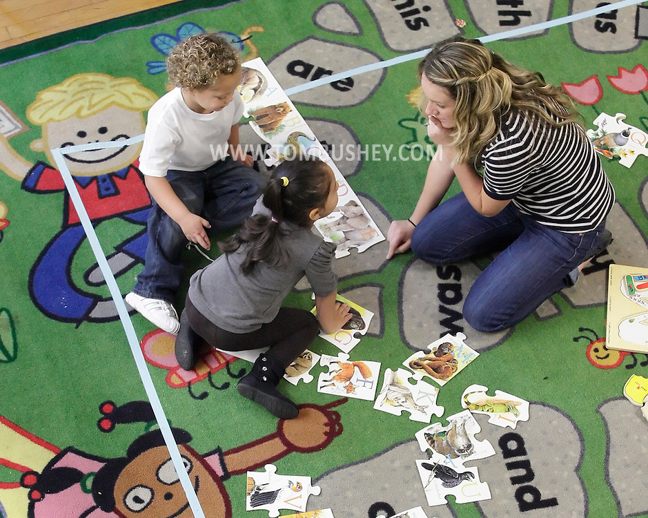 Teacher Lindsey Mitcheff helps Yaileen Jimenez, left, and Andreas Stephens, top, with an alphabet puzzle in a Head Start class at North Congregational Church in Middletown on Sept. 25, 2012.