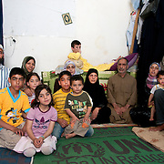 Jordan . Amman. Refugees from Syria. April 15th 2013. Some of the 18 people who live and sleep in this one room. Omar and his wife and 3 children. Malek and his wife, Noura. Omar's three sisters, one of their husbands and their children.
