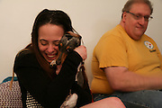 "Long Island, NY, March 31, 2016. Joelle, left, cuddles her 1-year-old Dachshund, Buddy. Mikey, right, and Joelle are hoping to be able to move into a place together soon, but the issue is complicated right now. ""I live at home with someone else and my 17-year-old daughter,"" said Mikey. ""It's been a while, but we need to make a change soon."" Mikey and Joelle have been dating for four years. He was the one who initially supported her in her treatment and would drive her to her doctor appointments in the city. 03/31/2016. Photo by Johanna Chisholm/NYCity News Service."