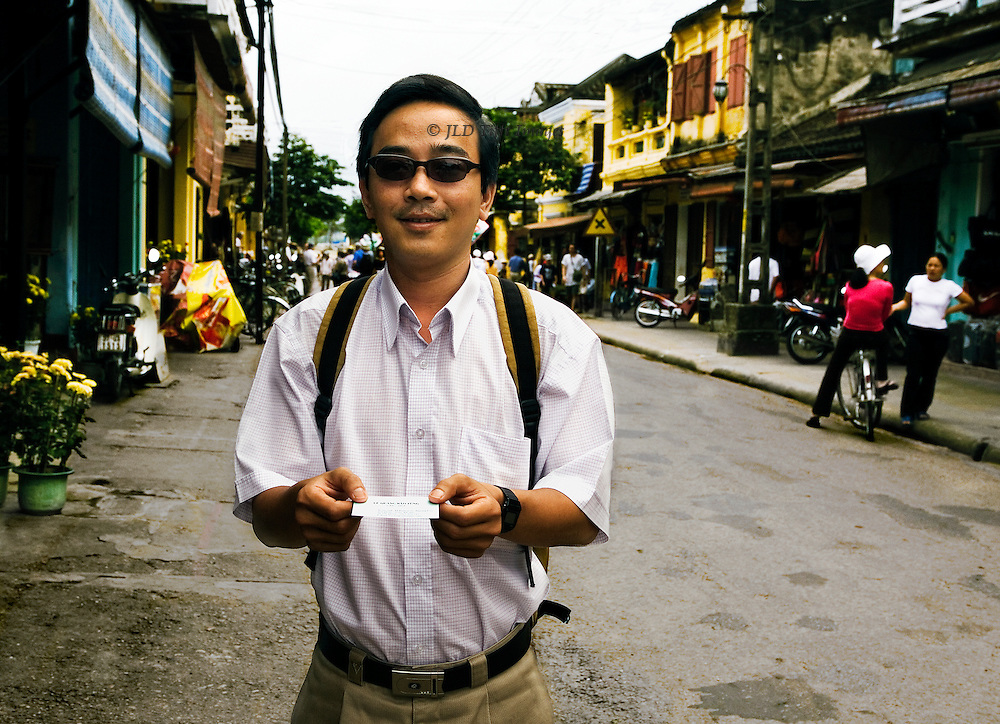 Young white collar worker wearing sunglasses demonstrates the customary Vietnamese courtesy of handing something to an older person with both hands.