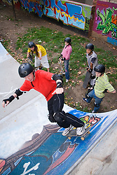 Teenagers having a lesson at a skateboarding park,