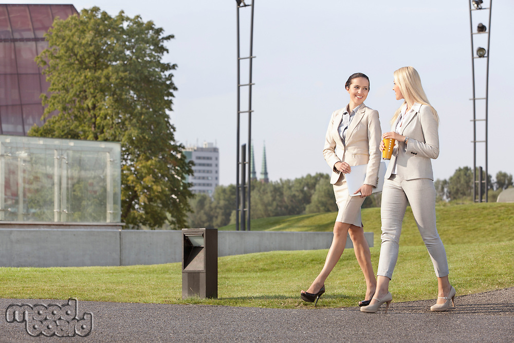 Full length of young businesswomen looking at each other while walking on street