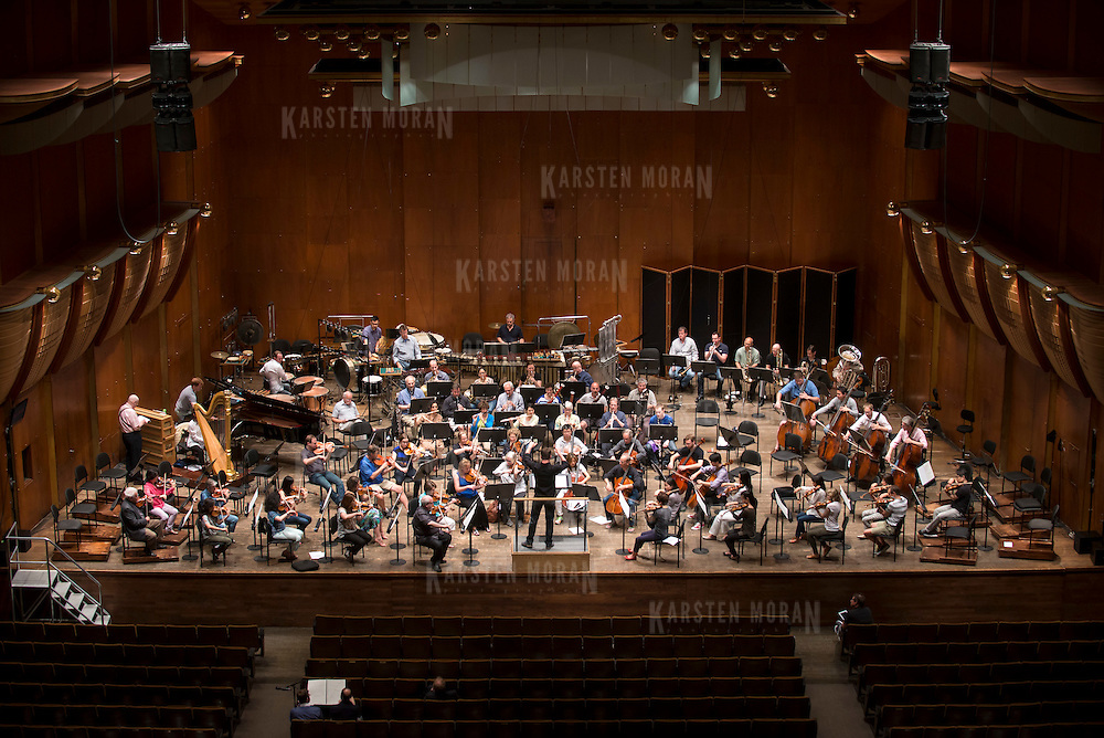 June 3, 2014 - New York, NY : As part of the New York Philharmonic Biennial, the orchestra solicited pieces from little-known composers and will choose three to play. Pictured here, conductor Matthias Pintscher, on podium at top center, leads the New York Philharmonic as it rehearses a composition by composer William Dougherty, who is visible at bottom left in center, working with mentor composer Derek Bermel on Tuesday. CREDIT: Karsten Moran for The New York Times