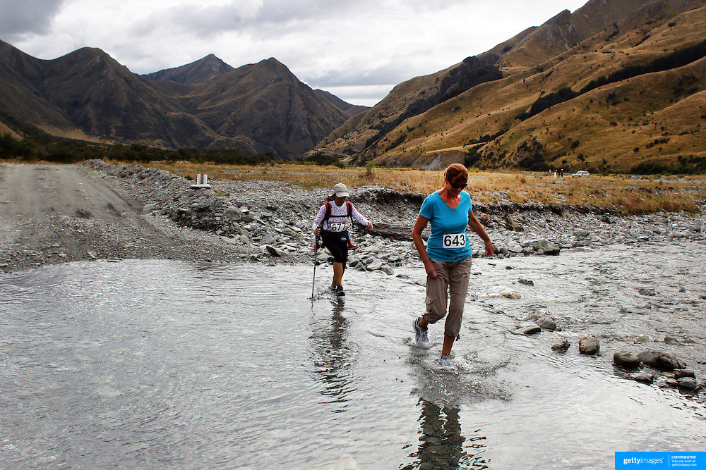 Runners Karelia Gonzalez (left) and Chantel Knox cross Moke Creek on the Ben Lomond High Country Station during the Pure South Shotover Moonlight Mountain Marathon and trail runs. Moke Lake, Queenstown, New Zealand. 4th February 2012. Photo Tim Clayton