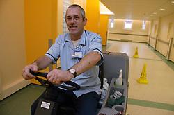 Housekeeper operating ride on scrubber drier machine down hospital corridor,