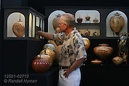Man admires ceramics for sale in artist's booth at the St. Louis Art Fair in Clayton, Missouri.