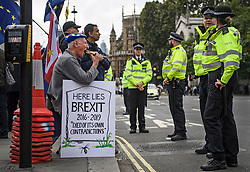 © Licensed to London News Pictures. 25/09/2019. London, UK. An anti Brexit protestor eats a sandwich while sat in front of police at the gates to the Houses of Parliament in Westminster on the day that MPs return to Parliament. The Supreme Court in London yesterday ruled that Parliament had been suspended illegally after British Prime Minster Boris Johnson prorogued parliament just weeks before the UK is due to leave the EU on October 31st. Photo credit: Ben Cawthra/LNP
