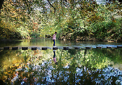 © Licensed to London News Pictures. 27/10/2015. Dorking, UK. A girl crosses the stepping stones over The River Mole near Box Hill . Photo credit: Peter Macdiarmid/LNP