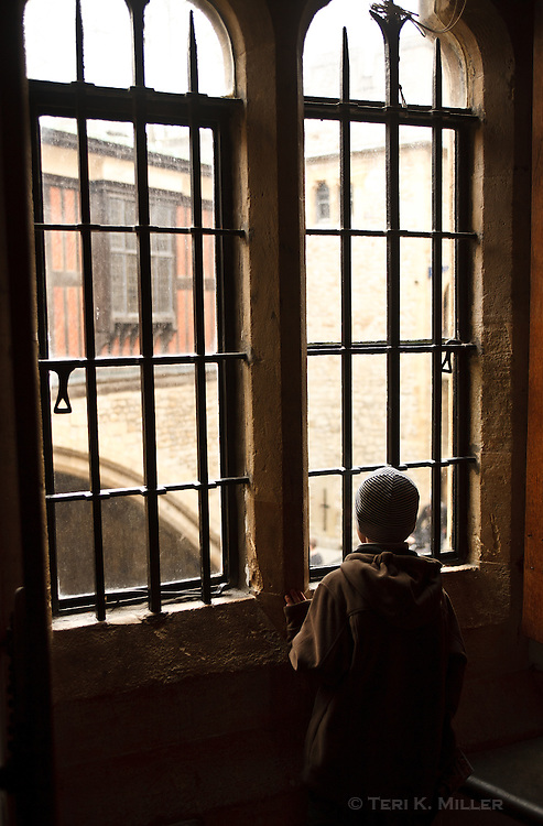 A boy looks out the window of the Medieval Castle at the Tower of London, London, England.
