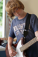 Boy (10-12) playing electric guitar in garage portrait