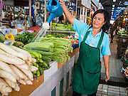 18 JULY 2013 - BANGKOK, THAILAND:  A vendor waters her produce in the Onnuch (also known as On Nut) Wet Market off of Sukhumvit Soi 77 in Bangkok.       PHOTO BY JACK KURTZ