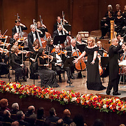 """November 11, 2012 - New York, NY : Accompanied by members of the Metropolitan Opera Orchestra and The New York Choral Society, and conducted by Patrick Summers (standing, right), mezzo-soprano Olga Borodina (standing to left of conductor) performs Camille Saint-Saëns's """"Mon coeur s'oevre a ta voix"""" from Samson et Dalila during the 2012 Richard Tucker Gala and concert in Lincoln Center's Avery Fisher Hall on Sunday evening. CREDIT: Karsten Moran for The New York Times"""