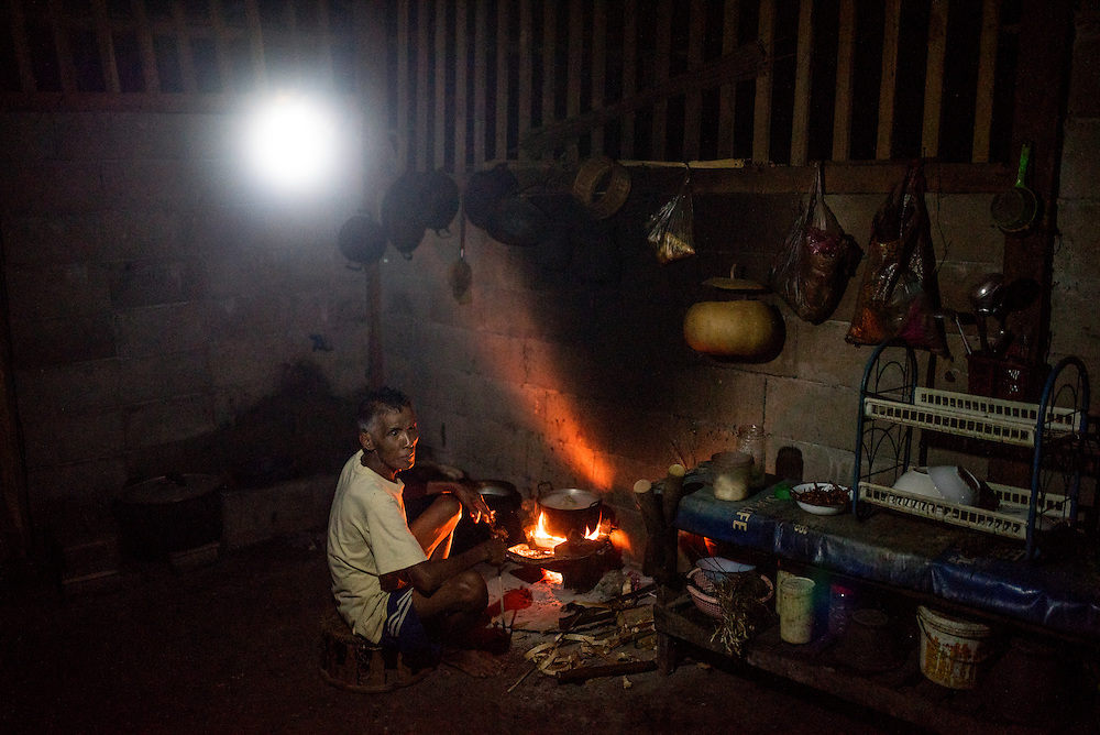 An elderly man cooks dinner under the light of an LED bulb powered by a portable water turbine in the village of Khoc Kham. The village is not connected to the main electrical grid and many residents operate their own turbines to power lights and sometimes small appliances.