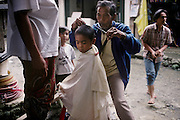 Street barber giving a haircut as children look on. Mount Diwata, Mindanao. The Philippines.