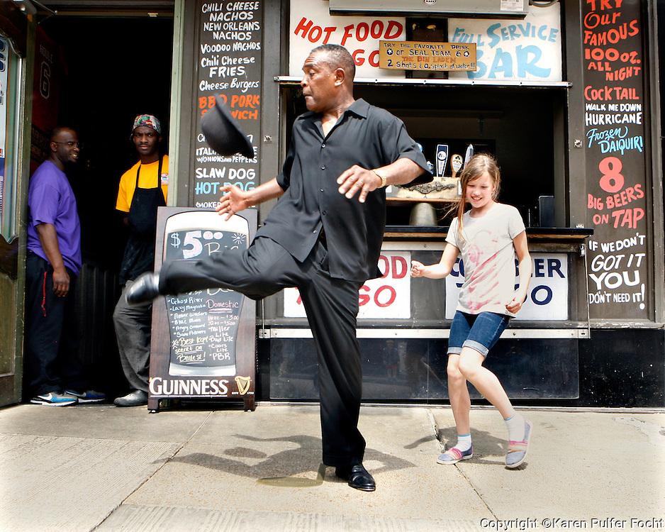 Tap Dancer George Nettles dances with a young visitor to Beale Street in Memphis. The girl wandered away from her parents, while they ate lunch, so that she could join him happily tap dancing down the street.