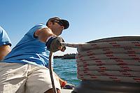 Sailor adjusting rope on boat