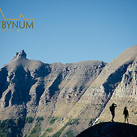 woman and young girl hike along ridge sillhouetted bishops cap and hanging garden crown of the continent